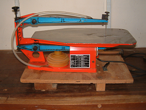 This is a used Hegner Multicut Scroll Saw mounted on a board which can be held firmly in a vice